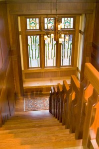 Art-glass windows decorate the stairwell of a new house in the California Arts & Crafts style.