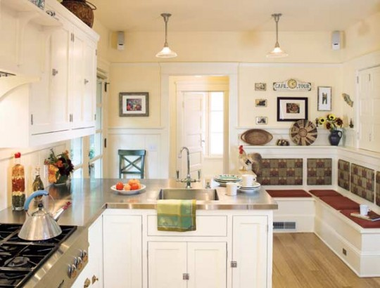 Stainless steel countertops, white-painted cabinets, and a new banquette enliven an expanded kitchen in a 1911 Foursquare