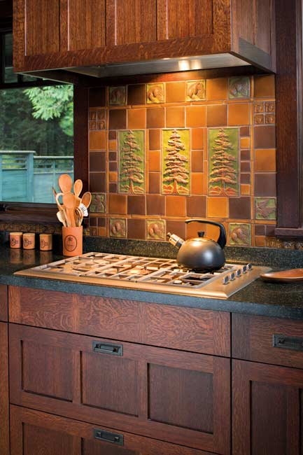Art tiles by Handcraft Tile Co. create an Arts & Crafts focal point over the range-top in a revival kitchen. Photo: William Wright