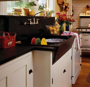 Cottage style comes from slant-front sink in stone and sunny yellow walls. Photo: Gross & Daly.