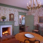 The dining room's table and chairs are in the American Queen Anne style of the mid-1700s. The ca. 1810 chandelier is French. Wallpaper is a historical pattern chosen by previous owners in the 1960s.