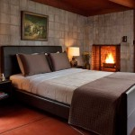 Exposed concrete block in the bedroom is warmed by a fireplace and redwood ceiling.