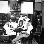 An old photograph shows kids playing cards in front of built-ins.