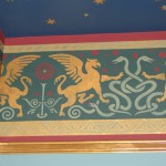 Griffins and snakes prance in the painted frieze 'Griffin'; stencil by Fly on the Wall Design.