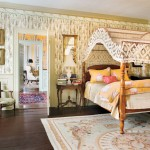 The master bedchamber is decorated with a trompe l'oeil wallpaper and frieze in imitation of swagged fabric. The antique bed is draped with a netted canopy. French chairs and carpet lend a Continental feel to this room.