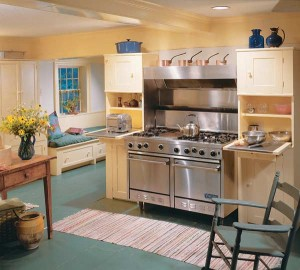 This kitchen allows the cook to do all food prep while seated at a sturdy country farm table or at pull-down shelving next to the stove. (Photo: Brian Vanden Brink)