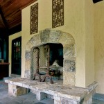 The outdoor fireplace's stone Tudor arch is a rustic counterpoint to those on the carved limestone mantels indoors.