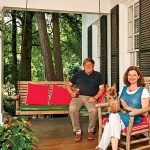 Anthony and Mary Ann Gilchrist relax on the front porch with their Yorkshire terrier, Lola.