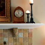 Rusted black iron candlesticks accentuate the red tones in the fireplace tiles.