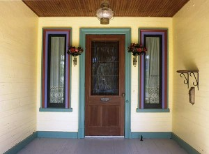 Harriet Paine and Alan Dargis have embraced endless home improvements including installing a welcoming stained glass panel on the front door, and painting a vivid palette to highlight the architecture.