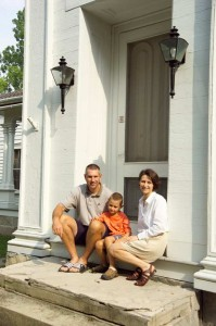 Alicia Campbell, husband Todd, and son Devin pose on the front steps of their Greek Revival house in upstate New York.