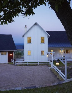 The house's façade is kept simple with board-and-batten siding. Breezeways connect the master suite on one side of the main living space and a recreation room on the other side.