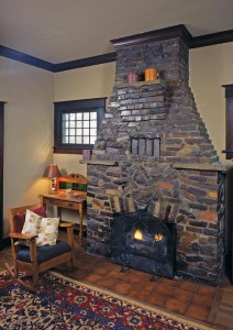 "Clinker bricks are mixed with other bricks in a style of masonry known as ""eccentric brickwork,""  which becomes less eccentric as it moves up into the chimney. Just above the firebox, bricks form the letter A, the initial of the first owners."