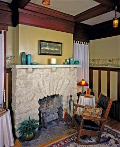 An arched limestone fireplace in another Memphis bungalow features a hearth of Rookwood tiles. The firebox is home to a set of 1930s vintage gas logs.