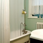 A restored clawfoot tub, relocated from upstairs, takes center stage in the refinished main bath.