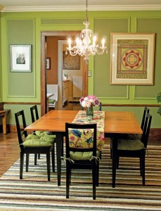 The couple repainted the dining room a mossy green and used a lighter shade to highlight the picture-frame moldings. They kept the room's existing  chandelier but eventually would like to replace it with an Arts & Crafts-style fixture.