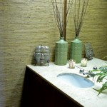 A bathroom highlighted by original wallpaper in a grass-cloth weave also harbors a unique period faucet.