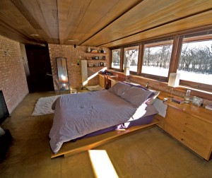 In the master bedroom, the platform bed and cabinets were designed by the architect himself, and made of the same cedar that defines the entire building inside and out.