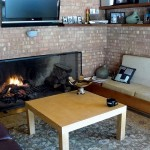 A massive fireplace spans nearly an entire wall of the living room.