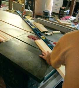 When feeding the molding stock into the blade, Brian rests his left hand on top of it as if holding a pool cue to keep the stock in alignment, being careful not to push it too close to the blade.