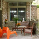 New orange molded chairs and a teak dining set occupy the covered patio beyond the glass doors, extending living space; the terrazzo floor is original.