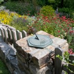 Coreopsis, salvia, and bee balm run riot behind the sundial on a stone pier.
