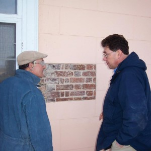 Mark Wenger (at right) checks out colonial-era brick liberated from pink stucco.