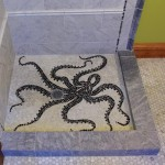 In the same bathroom, marble hex tiles create an octopus mosaic that traverses the shower pan.