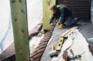 """Norris works to install the new threshold, which protrudes 7/8"""" above the old floor to help keep water out."""