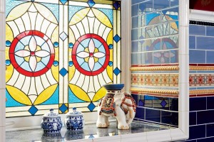 A custom-made stained glass window in a Chicago townhouse bathroom maintains privacy and light while adding color.