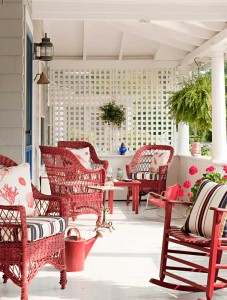 The red, white, and blue porch features Bar Harbor-style wicker furniture.