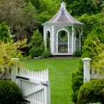 A gazebo provides a focal point against mature shrubs and trees, and offers views back to the house.