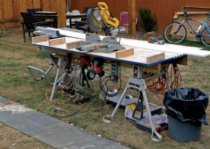 Mark made this work station using a sheet of plywood and some 2x4 blocks, all sitting on sawhorses bridged by 2x4s laid flat. Used to neatly organize tools, materials, and even coffee cups and cell phones, it keeps everything within easy reach, creating a tidy and efficient job site.