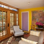 """Colors in the kitchen sitting room were inspired by the painting """"Interior with Calisimo,"""" which hangs near the purple door that leads up to bedrooms. The room then inspired the painting """"The Sun Room."""""""