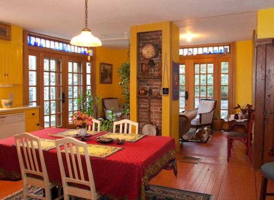 Nilsson added the antique French doors and transom lights for access to the garden and sunlight. The red, yellow, and blue theme is supported by the Aztec-red floor, 'Viking Yellow' walls, and blue glassware.