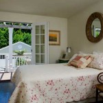 French doors open to the terrace and a garden view in the guest bedroom on the main floor. The quilt is Provençal.