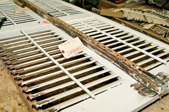 The deteriorated shutters are disassembled for stripping.