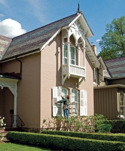 Ted Robertson hangs the good-as-new shutters on the Gothic Revival house.