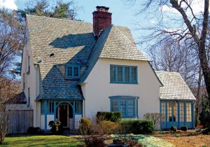 A fine Arts & Crafts house shows a very steep two-story gable and variegated slate roof.