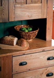 Simple unfinished wood cupboards in the pantry keep the look historical.