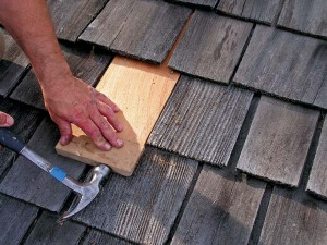 Buffering the hammer from the shingle with a block of wood prevents damage to the new shingle.