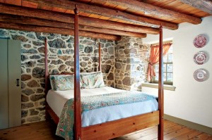The master bedroom's exposed stone wall contains a flue for the dining-room fireplace, which was too damaged to save.