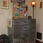The industrial metal cabinet, a flea-market find, holds a colorful collection of vintage travel brochures displayed in an old gas-station caddy that held road maps.