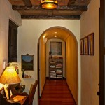 Mahogany flooring extends into all private spaces of the house, including a hallway that connects bedrooms. The ceiling fixture is a reproduction.