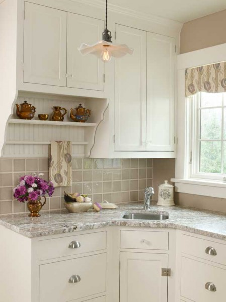 Honed granite countertops, beige tile, and a Mackintosh-print valance and tea towel add subtle layers of color to a Colonial Revival kitchen.