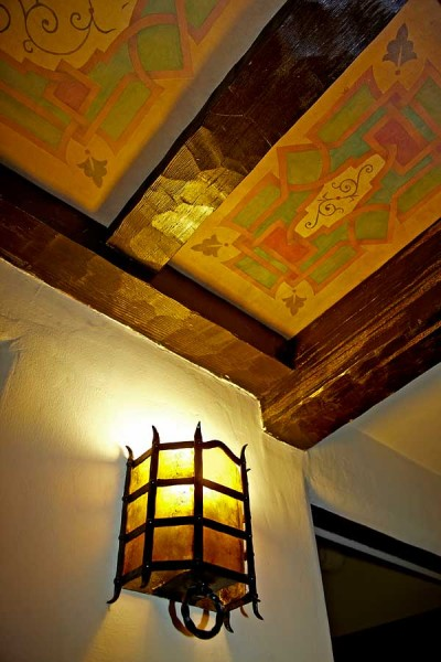 Not all accent lighting has to be contemporary. This original California Mission sconce washes the wall just enough to illuminate paint decoration between the beams.