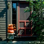 At the front door, an old concrete urn elevates fall pumpkins.