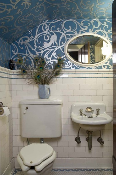 For owners of a 1908 Tudor house in Seattle, a tiny attic bathroom provided the perfect space to go bold—the hand-painted silver and blue pattern lining the walls and ceiling was inspired by an antique cobalt and silver vase.
