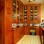 The butler's pantry has a six-arm Anglo–Dutch brass chandelier; owner Judi Heise made the painted floorcloth to protect the wood floor. Cabinets are original except for some refurbished glass doors