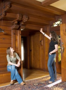 Both women have come to appreciate the house's architectural details, including its exotic wood, such as teak, and the rounded edges of these protruding beams in the entry hall.
